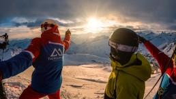Panorama, Skifahrer zeigen in Richtung Sonnenuntergang
